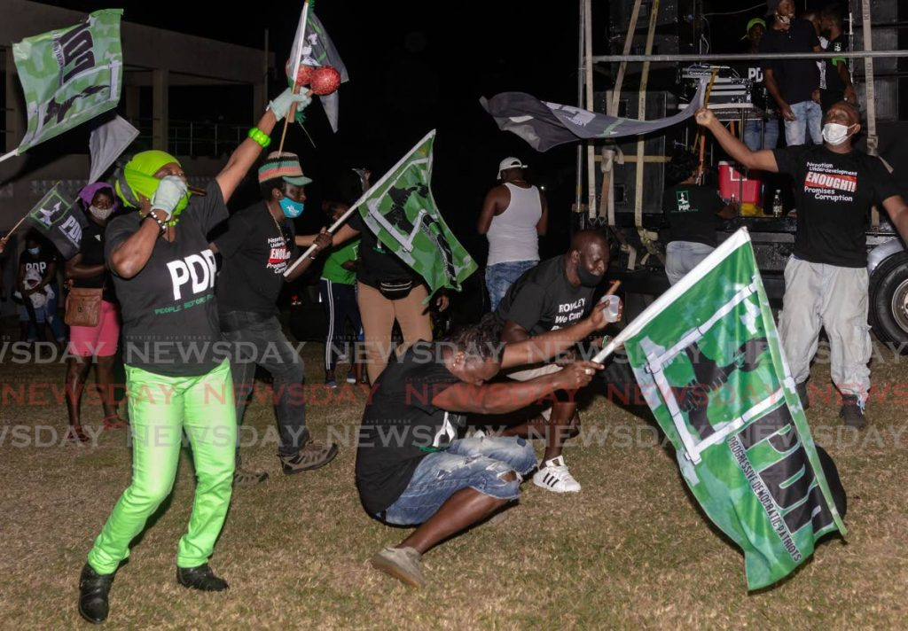 PDP supporters wave flags at a meeting at Signal Hill Recreation Ground last Thursday. - DAVID REID
