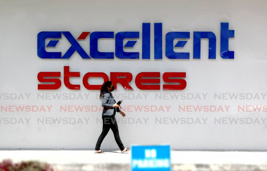A woman walks past an Excellent Stores sign at the Shops of Arima at Cocorite Road in Arima last week/ - ROGER JACOB