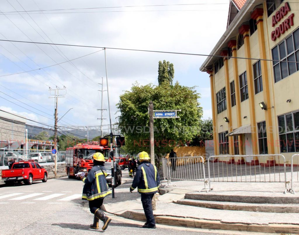 Fire officers secure the area around Agra Court, Patna Street, St James where a fire broke out on Monday. - Angelo Marcelle