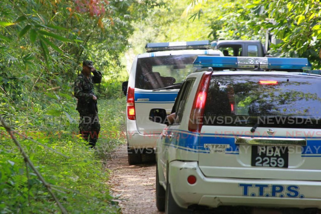 A soldier waits to join the police search for kidnap victim Andrea Bharatt in Sangre Grande. PHOTO BY ROGER JACOB -