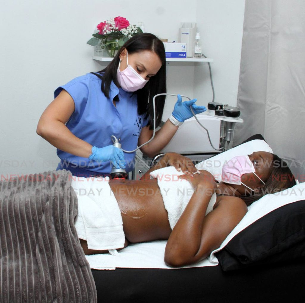 Body contouring specialist Chanelle Talma-Da Costa performs an ultrasonic cavitation on Queenith Assee at BodySculpTT, Woodbrook.  Photos by Angelo Marcelle