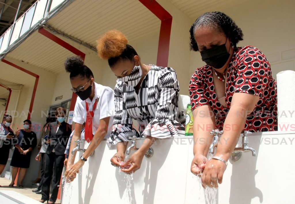 Minister of Education Dr Nyan Gadsby-Dolly, centre, washes her hands by a pipe at St James Secondary School along with form five student Amelia King and Minister in the Ministry Lisa Morris-Julian on Monday. PHOTO BY AYANNA KINSALE -