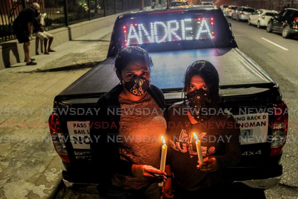Reshma Mohammed and her daughter Arianna hold candles outside the Red House, Port of Spain, on Monday during a vigil for murder victim Andrea Bharatt and others who lost their lives to violent crimes. PHOTO BY AYANNA KINSALE -