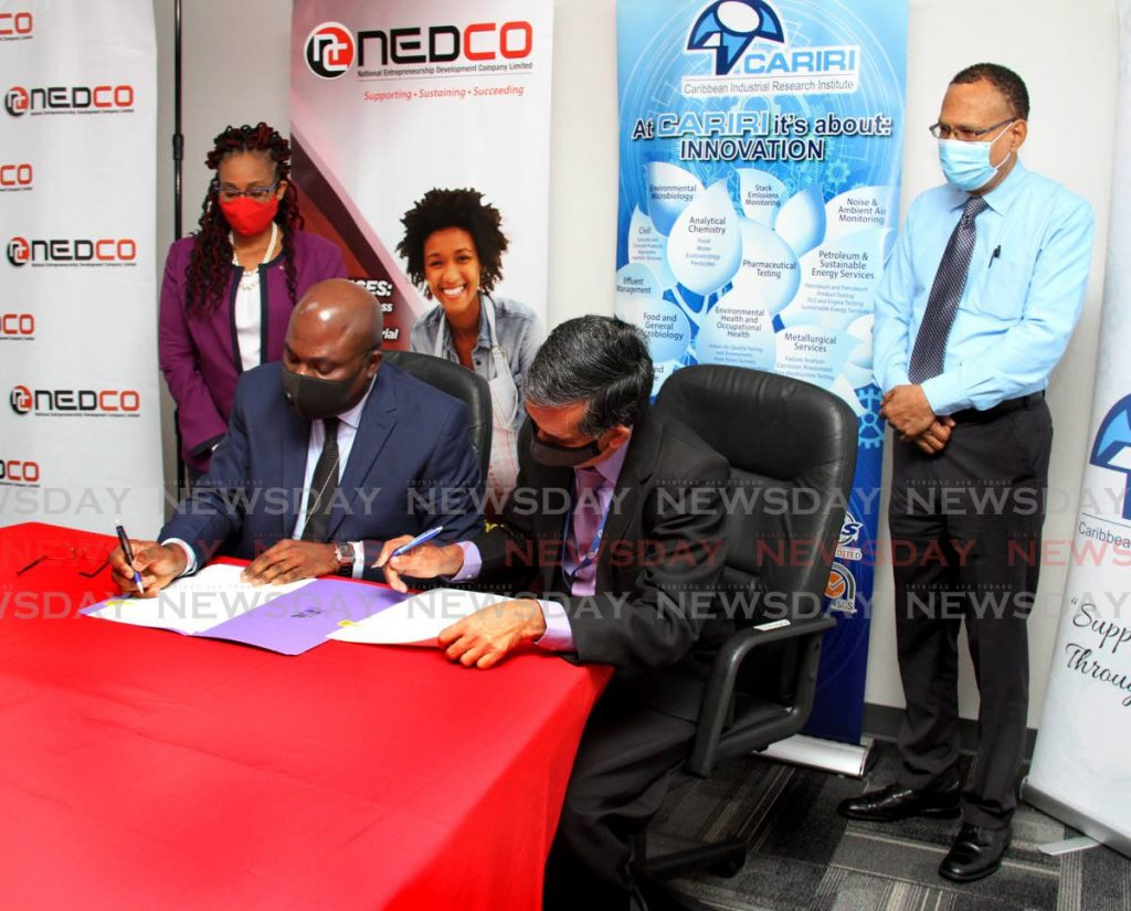 NEDCO CEO Calvin Maurice, left and CARIRI executive manager, corporate services, Meghnath Gosein, sign an MOU for the provision of business development services at NEDCO head Office, Queen's Park East, Port of Spain on February 8. Witnessing the signing are NEDCO chief entrepreneurial development officer Karen Carraballo and programme co-ordinator Robert Nunes. - Angelo Marcelle