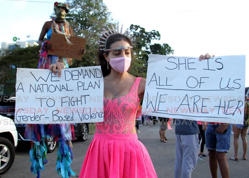 A costumed woman holds signs demanding a national plan on gender-based violence during a march by Women in Carnival around Queen's Park Savannah, Port of Spain last Monday. PHOTO BY AYANNA KINSALE -