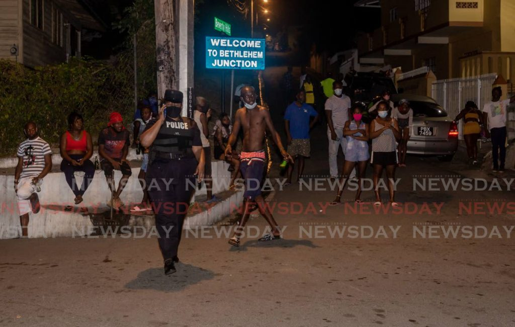 Residents of Bethel look on as police cordon off the scene after a multiple shooting on Monday night. - DAVID REID