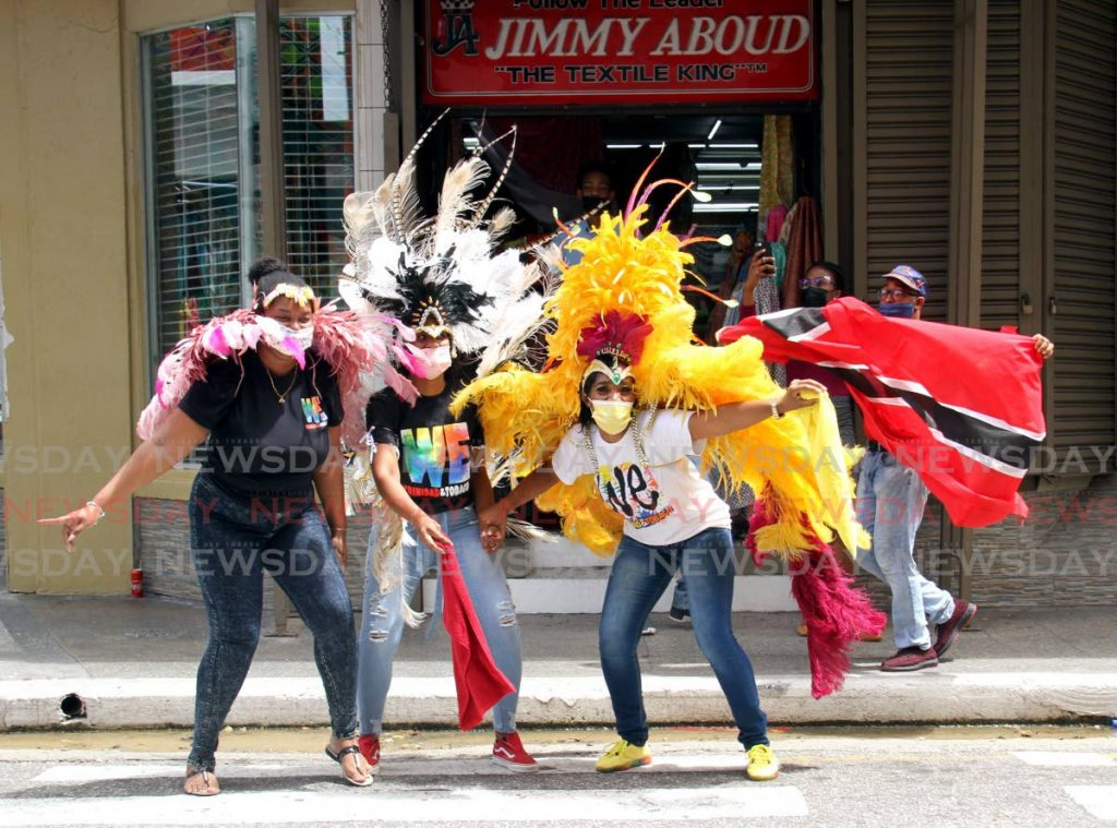 LUNCHTIME WINE: Staff members of Jimmy Aboud cloth store get into the Carnival spirit with an impromptu jump up in front of the store's Henry Street, Port of Spain outlet. PHOTO BY AYANNA KINSALE -