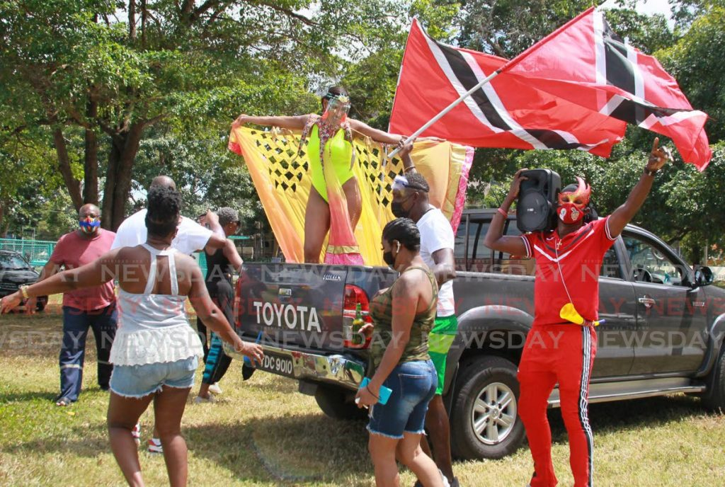 Revellers have fun around a van at the Queen's Park Savannah as they enjoy music from NEXT 99.1FM broadcasting from a YUMA truck nearby. PHOTO BY ROGER JACOB  -
