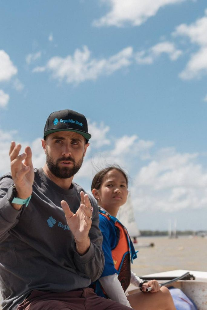 Olympic sailor Andrew Lewis guides a young sailor at the Andrew Lewis Sailing Foundation 'Mentoring through Sailing' programme at Vessigny Beach over the weekend.  - Melvern Isaac
