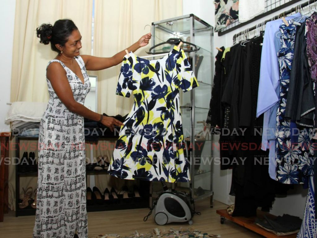 Alana Ramlal, manager of Up Boutique at Queen's Park Oval, Port of Spain, shows some of the work clothes available at the boutique. PHOTOS BY AYANNA KINSALE -