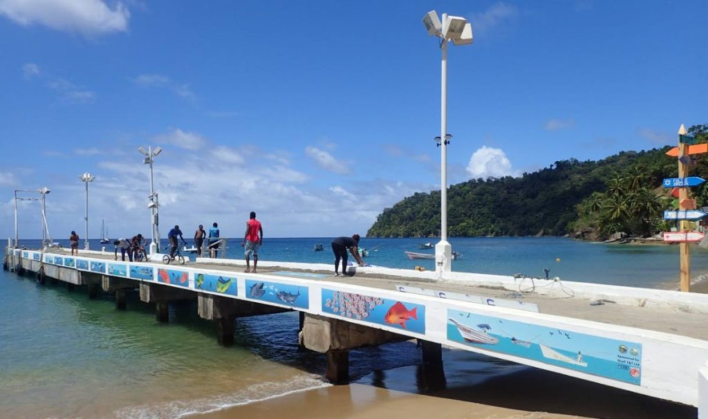 Charlotteville Jetty with murals showing fishing boats, yachts and natural heritage in the North East Tobago UNESCO Man and the Biosphere Area. -