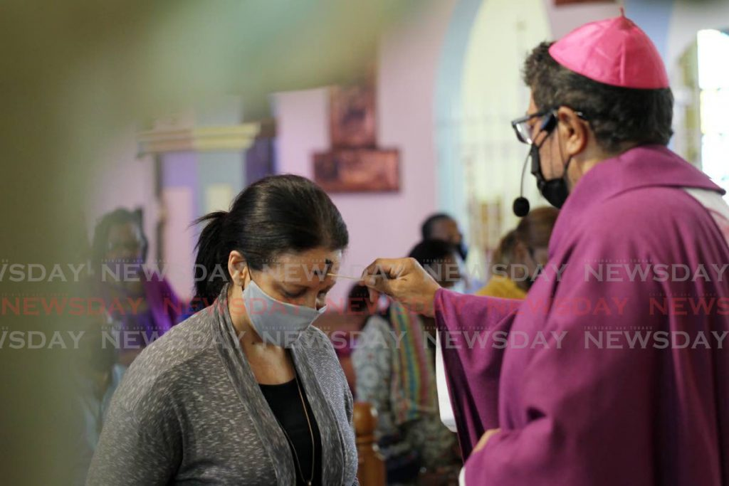 A parishioner is marked with a Q-tip by RC Archbishop Jason Gordon on the forehead at the  Ash Wednesday mass at Our Lady of Perpetual Help Church, Harris Promenade, San Fernando. - Lincoln Holder