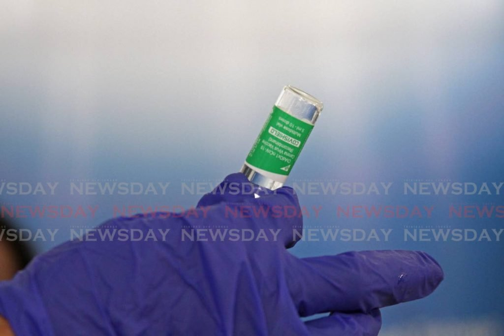 In this February 28 file photo, a health worker examines one of the Oxford Astrazeneca covid19 vaccines earlier this month when healthcare workers were administered the shots at the Couva Hospital. Photo by Marvin Hamilton