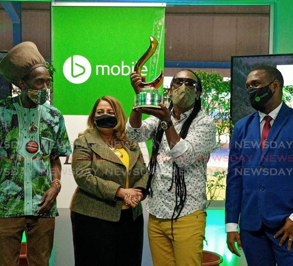 Farmer Nappy, second from right, holds the trophy after he was named the winner of the bmobile/TUCO online road march on Wednesday at the TSTT hospitality suite, Queen's Park Oval, Port of Spain.  - MELISSA DOUGHTY