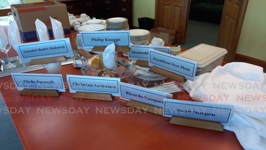 Bailiffs gather desk name plates of board members of the Education Facilites Company Ltd (EFCL), dinnerware and glasses during a levy on the state-company on Thursday.