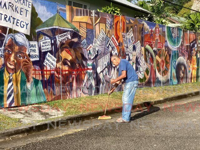 Artist Jackie Hinkson keeps a clean scene at his outdoor Carnival-themed exhibition. -