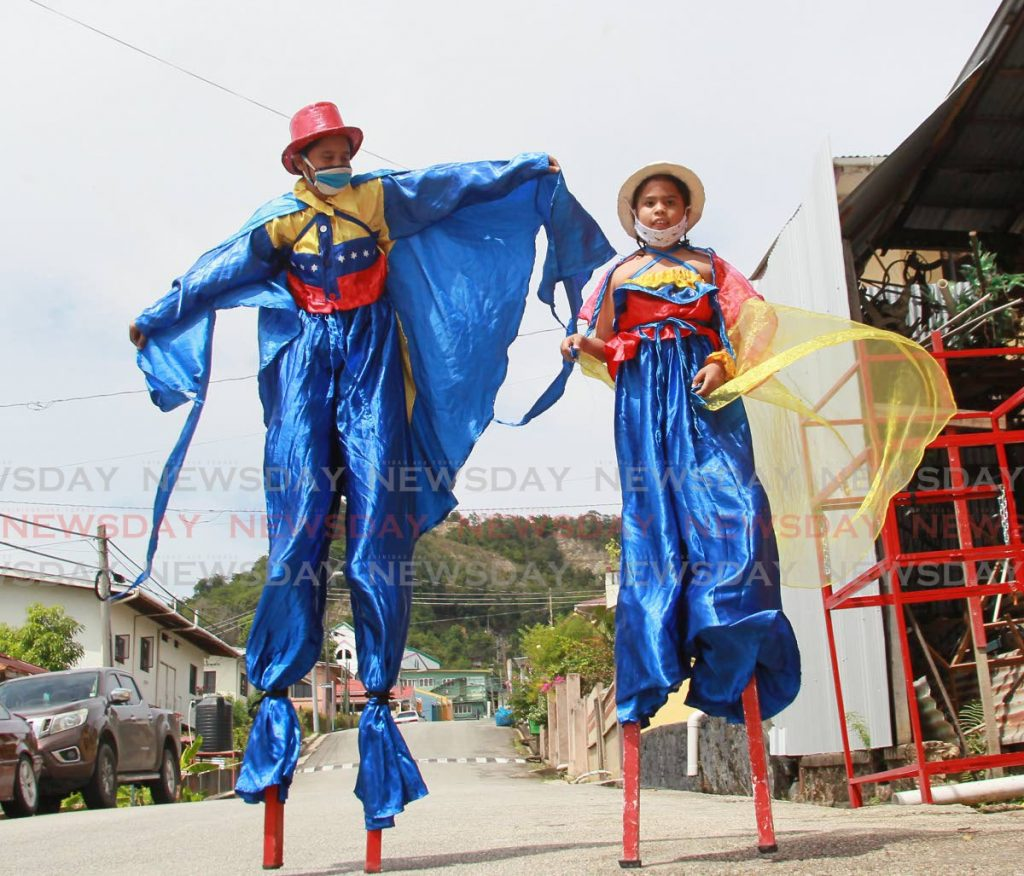 Riannel Jose Mendoza Salazar and his sister Rihanna Mercedes celebrate their home country Venezuela in moko jumbie portrayals on Henry Street, San Fernando. -