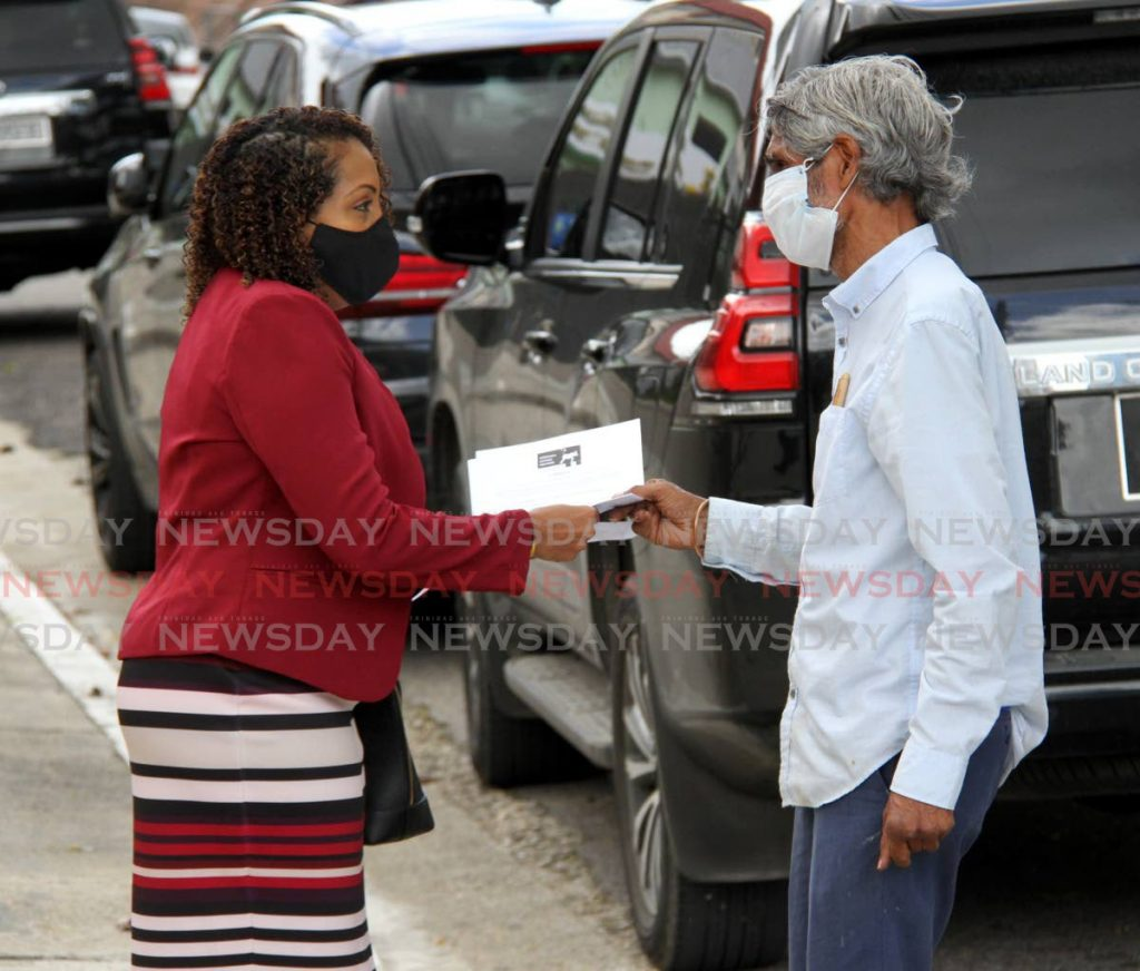Dr Wayne Kublalsingh gives Tabaquite MP Anita Haynes a proposal on law reform for the criminal justice system at the Red House, Port of Spain, on Friday. - Angelo Marcelle