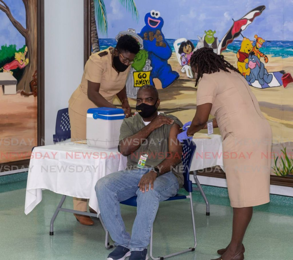 Dr Ogonna Okeke, centre, of the Scarborough General Hospital gets his covid19 vaccine at the Scarborough Health Centre, in Tobago on Saturday. PHOTO BY DAVID REID -