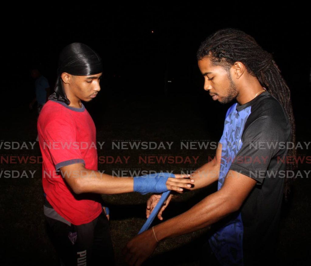 Jarel Nunes, right, wraps the hand of a young boxer before training. - Angelo Marcelle