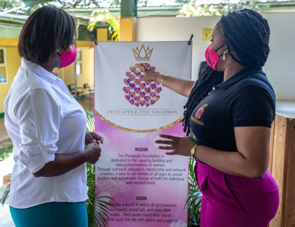 Minister of Sport and Community Development Shamfa Cudjoe asks founder councillor Nicole M Young about the symbolism of the logo. -