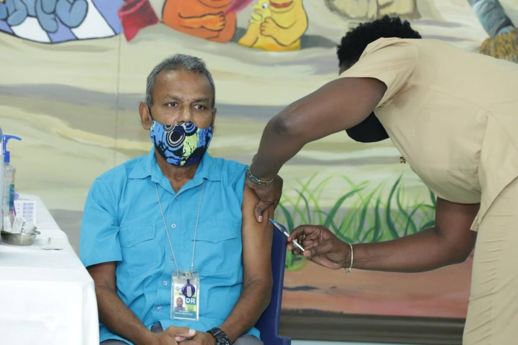 Dr Ian Sammy, head, Accident and Emergency Department, Scarborough General Hospital receives the Oxford-AstraZeneca vaccine from Nurse Beryl Samuel-Gray, District Health Visitor, on Saturday. PHOTO COURTESY DIVISION OF HEALTH -