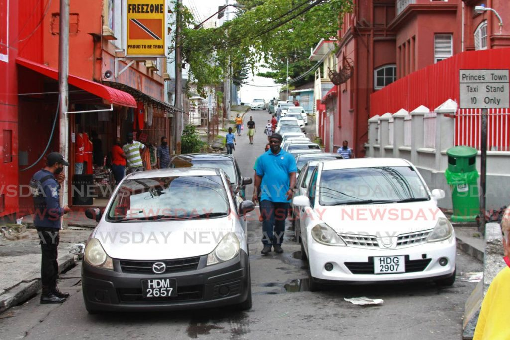 A police officer on the Princes Town Taxi stand spoke with a driver, one of which were seen wearing a red shirt as part of the new uniform imposed by some members of the association. - Marvin Hamilton