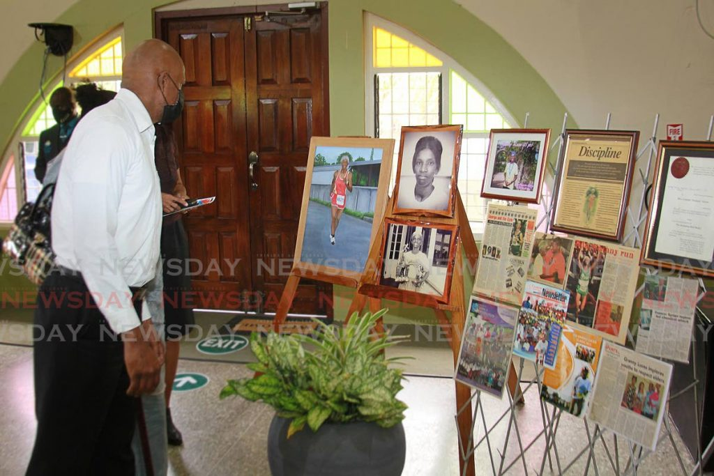 People gather to view photographs of the late long-distance runner Lynette 'Granny'  Luces, at her funeral, on Thursday at the Mt D'Or Seventh Day Adventist Church. - ROGER JACOB