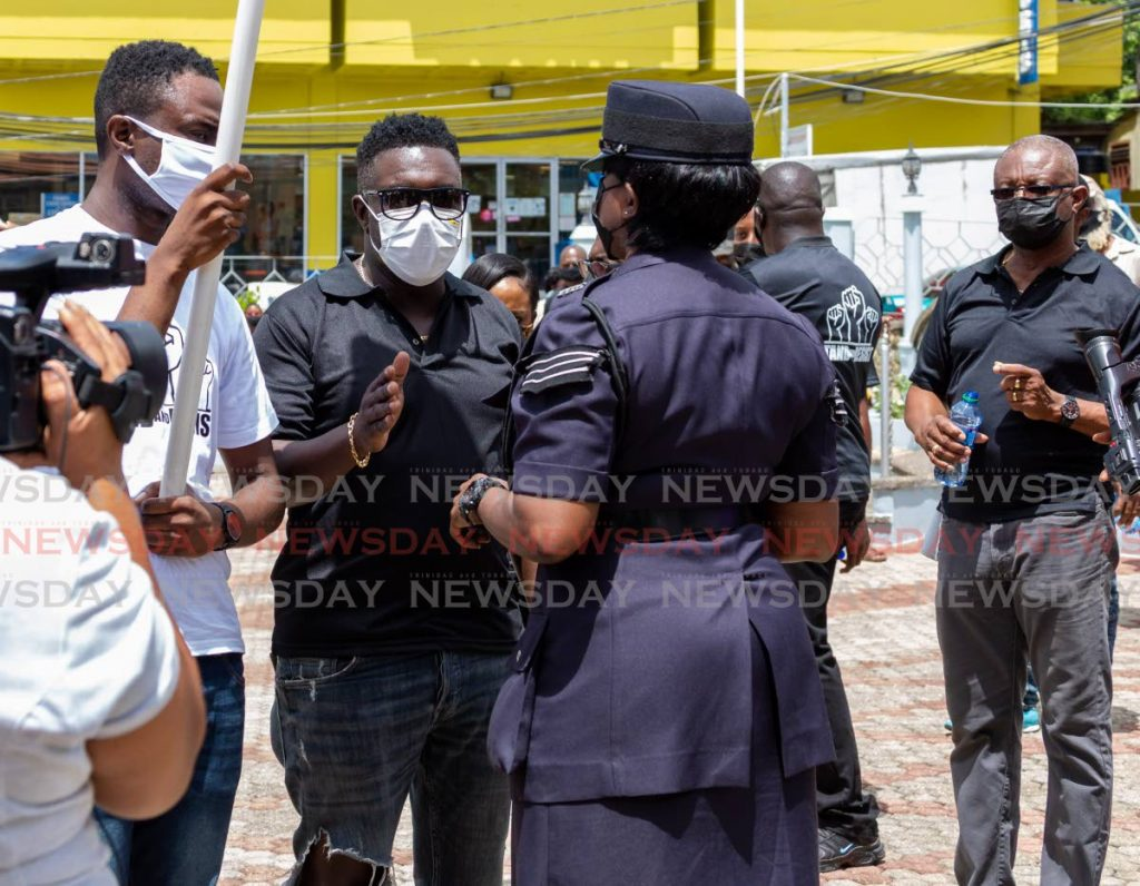 A policewoman warns PDP's political leader Watson Duke and deputy leader Farley Augustine about marching illegally in Scarborough on Friday.  - DAVID REID