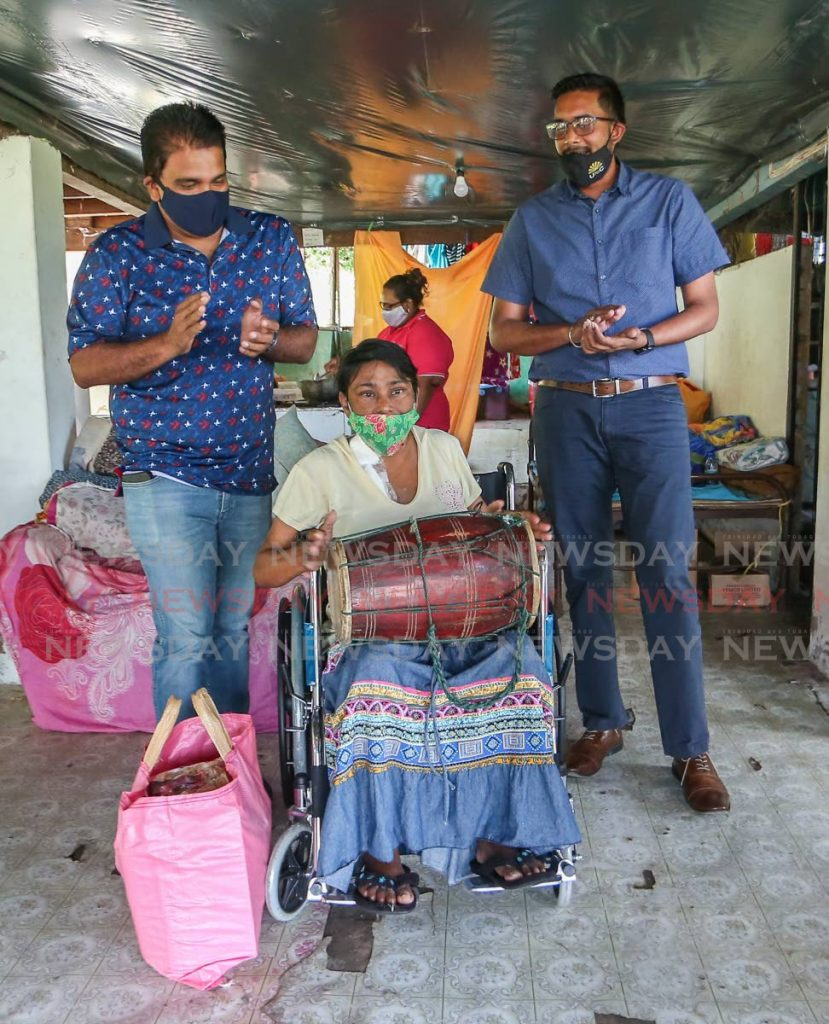 Haspathi Singh plays a tabla after Oropouche East MP Dr Roodal Moonilal and councillor presented her with a wheelchair at her home in Debe. Photo by Jeff Mayers. -