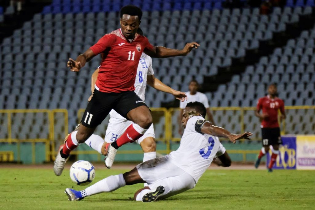 In this Oct 10, 2019 file photo, TT's Levi Garcia, left, dribbles past Honduras' Maynor Figueroa during a Concacaf Nations League match at the Hasely Crawford Stadium. Garcia scored the first goal against Guyana, on Thursday, in TT's first World Cup qualifier, in the Dominican Republic. - AFP