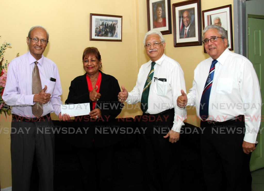 President of the Princess Elizabeth Home for Handicapped Children Doctor Calvin Inalsingh, left, and CEO Jan Sirjusing hold up a donation received from Freemasons of TT members Rajendra Bhagwat, second from right, and Gerald Mendes at the home on Ariapita Avenue, last Friday. - Ayanna Kinsale
