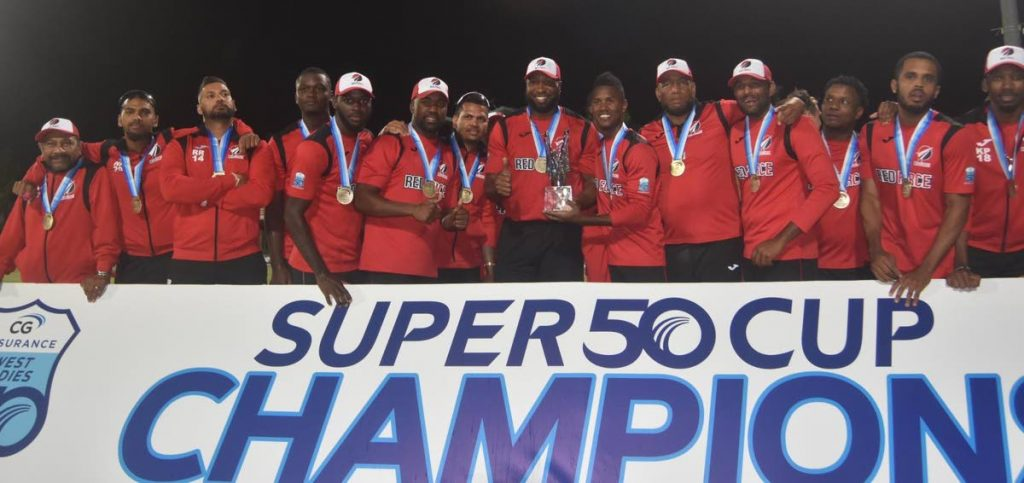 Red Force players celebrate with the Super50 trophy after beating Guyana Jaguars in the final at the Coolidge Cricket Ground, Antigua, Saturday. - CWI