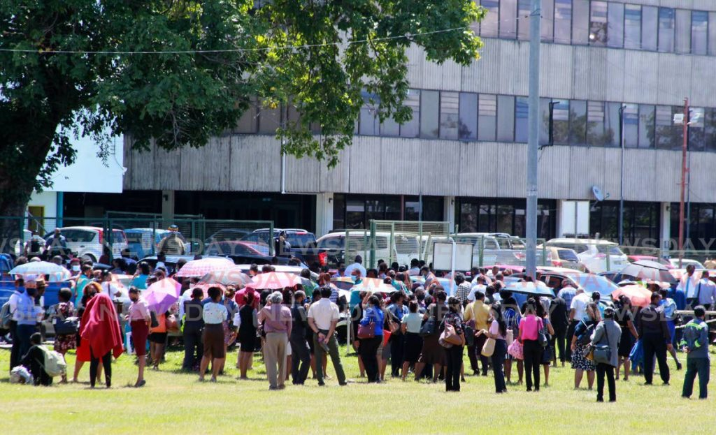 WASA workers who showed up for work on a day their trade union urged them to say home gather outside the St Joseph head office after a fire alarm was triggered in the building. PHOTO BY ROGER JACOB -