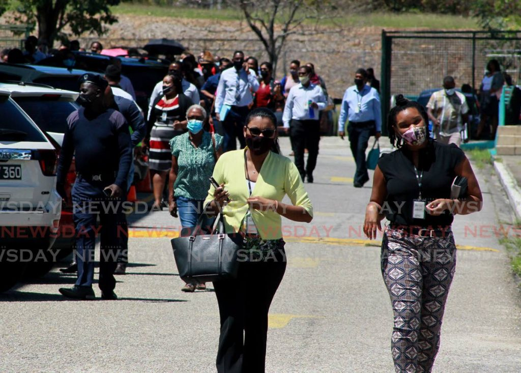 BACK TO WORK: WASA workers head back to work after the all-clear was given after an alarm was triggered at the utility's St Joseph head office on Tuesday. PHOTO BY ROGER JACOB -