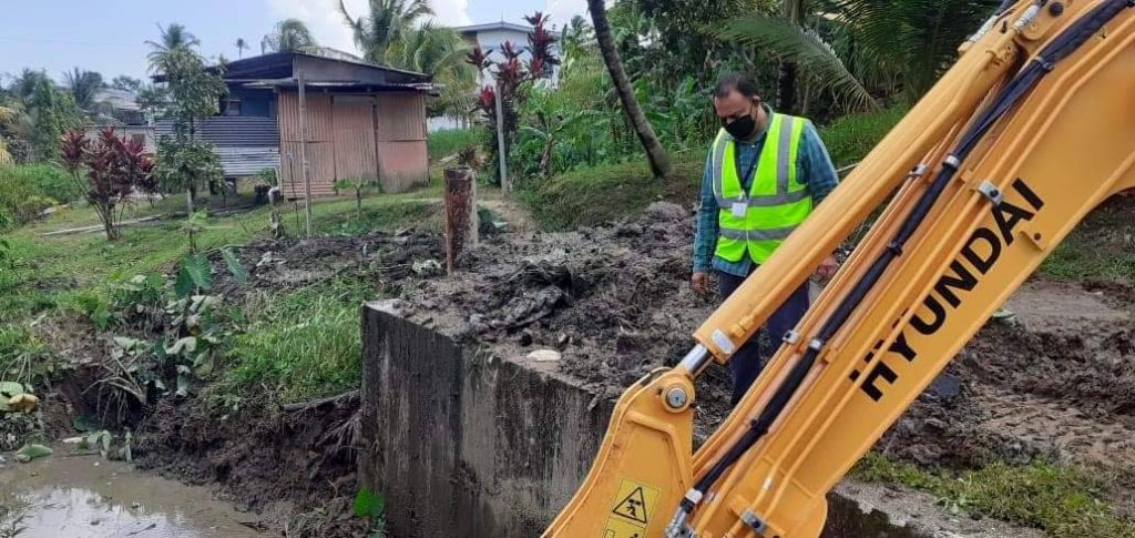 Chairman of the Sangre Grande Regional Corporation Anil Juteram oversees the clearing of a watercourse along Robinson Circular, Toco, Sangre Grande. Photos courtesy Sangre Grande Regional Corporation