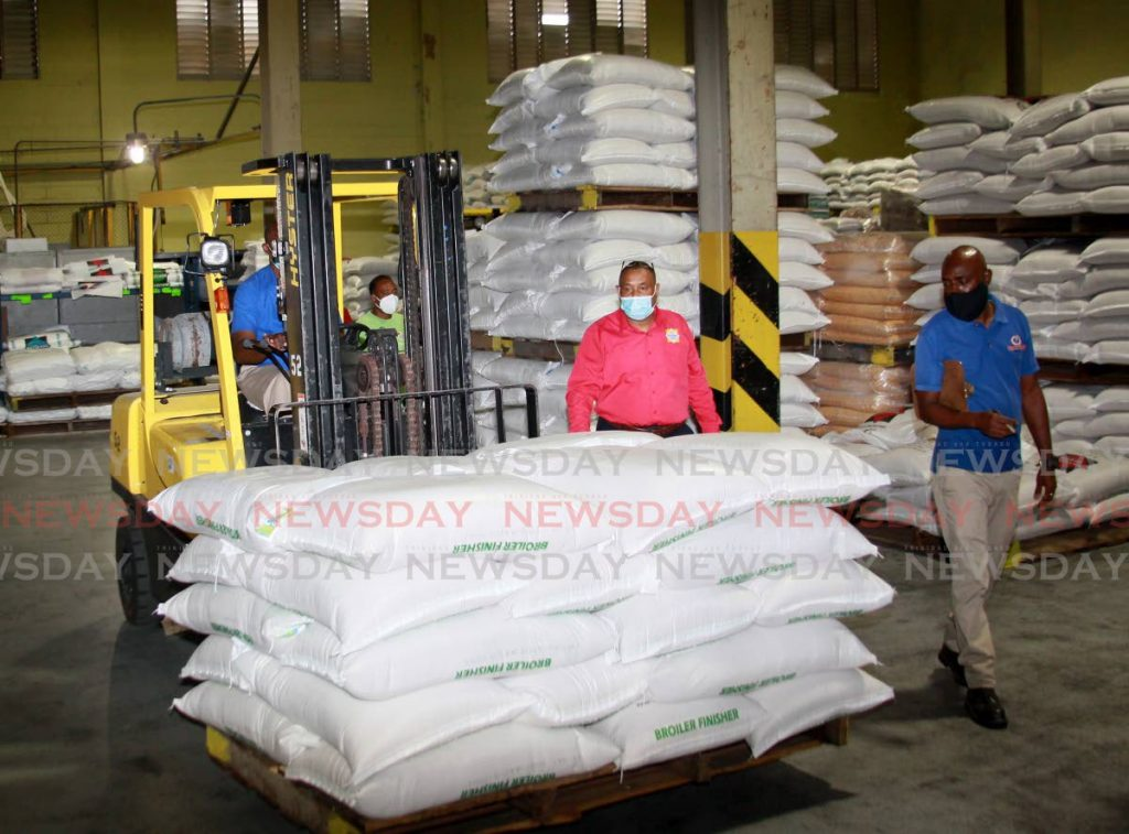 FILE PHOTO: Workers at National Flour Mills, move chicken feed at the company's warehouse on Wrightson Road, Port of Spain. -