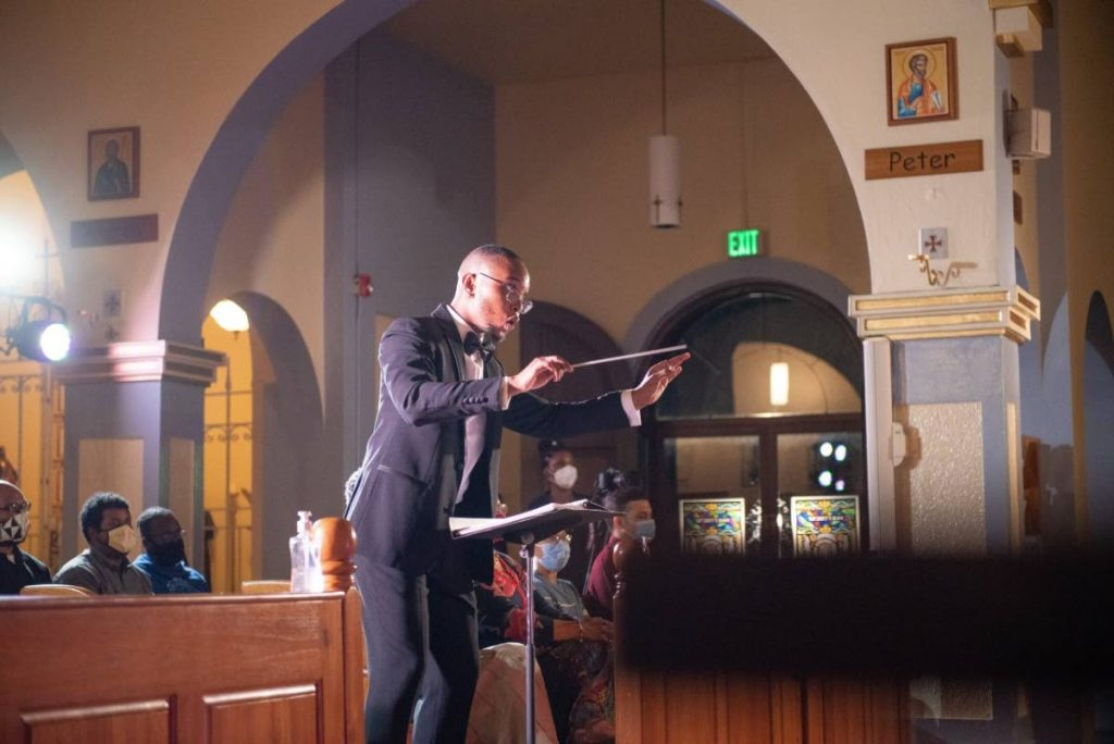 Michael Hudlin conducting a small chorus for And On Earth Peace, Christmas 2020 at the Pro-Cathedral of Our Lady of Perpetual Help, San Fernando.  -