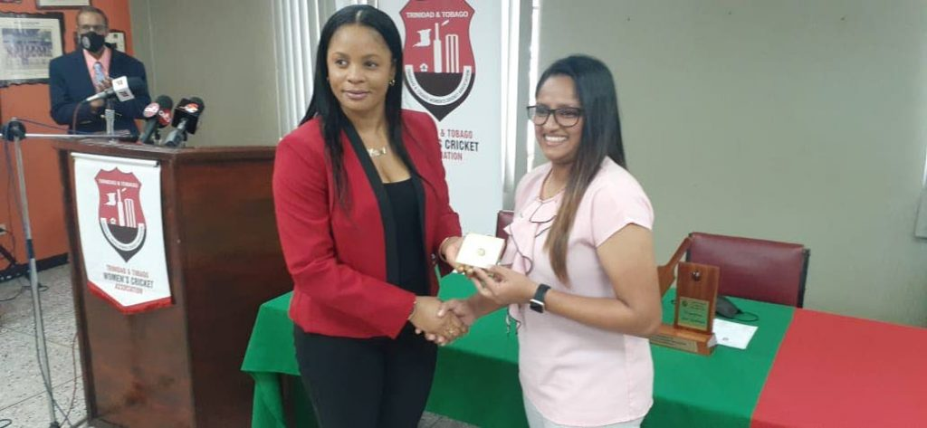 Merissa Aguilliera , left, presents Anisa Mohammed with a ring inscribed with Mohammed's initials and her playing kit number on behalf of the TT Women's Cricket Association, at theNational Cricket Centre, Couva, on Monday. - Photo courtesy TTWCA