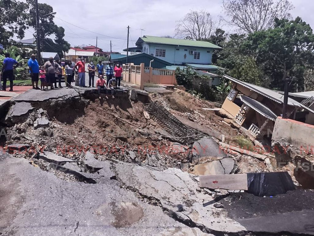 In this file photo taken on March 17,  concerned residents of Mandingo Road, Princes Town look at the landslip which has disrupted their lives. -