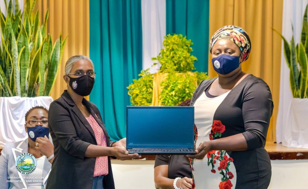 School Supervisor III SherryAnn Rollocks-Hackett makes a presentation to Principal of the Bishop's High School Cindy Ramnarine during the division's handing-over ceremony for devices at the Scarborough Library  - THA PHOTOS