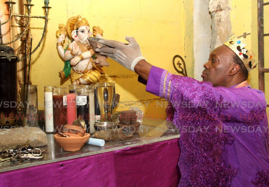 Archbishop Dr Jeremiah Mason offers jal (an offering ) to the elephant-headed Hindu God, Ganesh, at the Holy Trinity Baptist Cathedral, St Joseph. Mason also displayed Islamic prayers he received from a Muslim man he assisted. Photo by Ayanna Kisnale