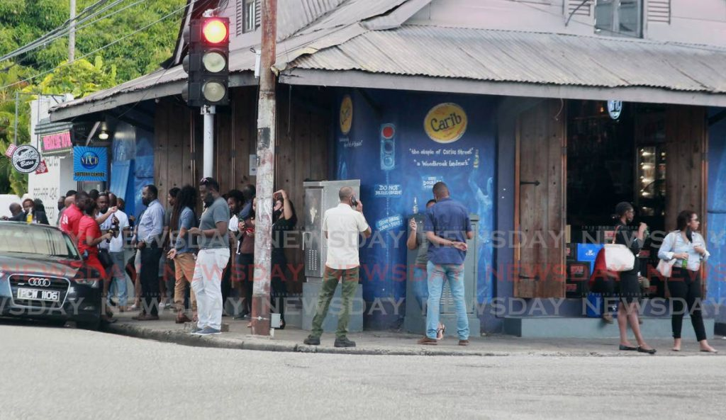 Limers drink outside Brooklyn Bar, Woodbrook last month.  File photo by Roger Jacob