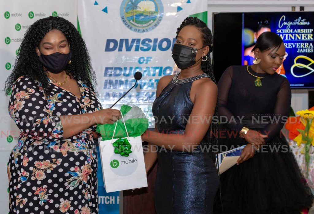 Scholarship winner Treverra James, right, collects a gift from Onika Blackman, left, manager of Enterprise Sales, Marketing and Communications, Bmobile, at a function on Tuesday.   - DAVID REID