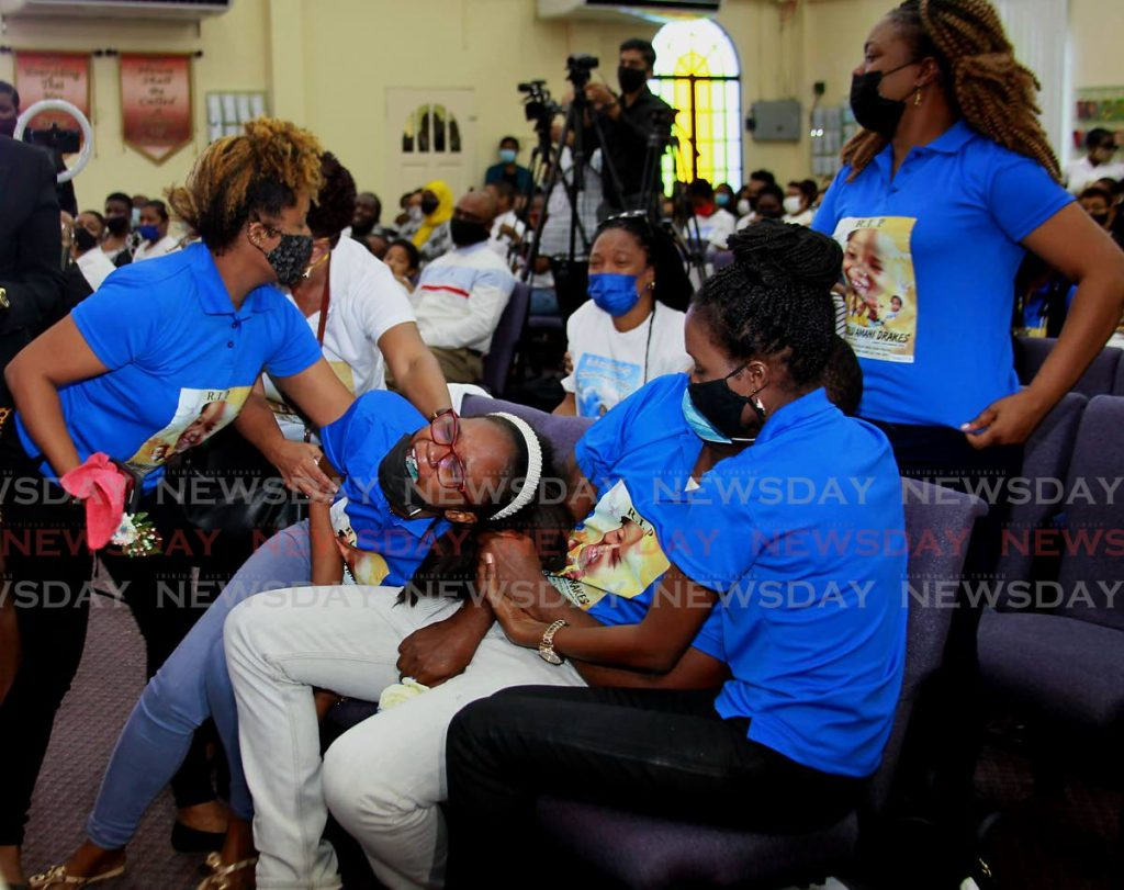 Two-year-old Romelu Drakes' parents, Regine Phillip and Shion Drakes, centre, are comforted by relatives at the toddler's funeral at the Balmain Worship Centre, Couva Main Road, Couva, on Wednesday. - ROGER JACOB