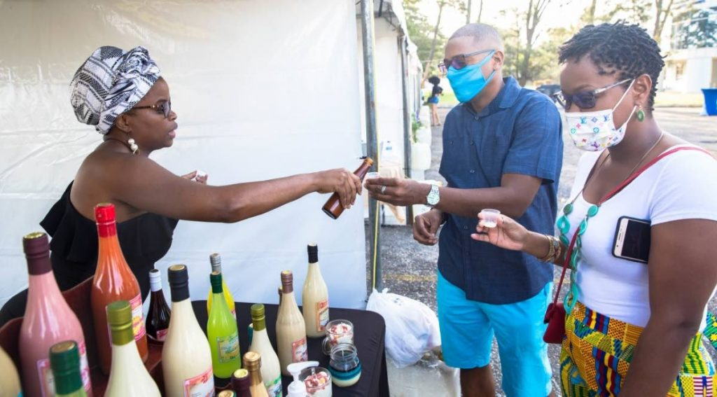 A vendor serves visitors ponche-de-crème samples at the Sunalia Christmas market held on December 6 at Cipriani College of Labour and Co-operative Studies, Valsayn. Some 40 vendors will participate in the  sunset market at Mount Irvine Bay Resort Tobago.  Photo courtesy Kelton Francis -
