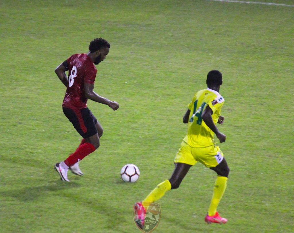 In this photo taken on March 25, TT captain Khaleem Hyland (left) moves past Guyana midfielder Daniel Wilson during the 2022 FIFA World Cup Concacaf Zone qualifier at the Estadio Panamericano, San Cristobal, Dominican Republic. PHOTO COURTESY TTFA -