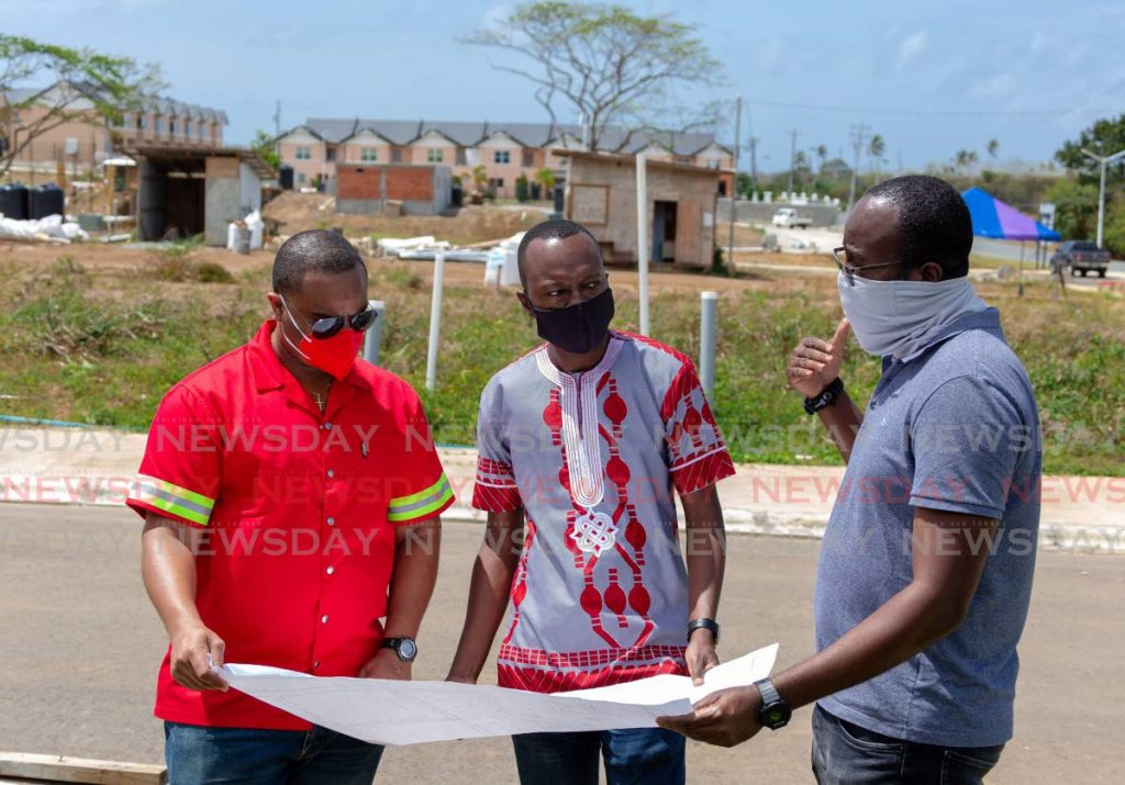 Chief Secretary Ancil Dennis (center); Councillor Kwesi Des Vignes, Secretary of Infrastructure, Quarries and the Environment; and Abdallah Chadband, senior technical coordinator view the plans for the Shirvan Land Development at Shirvan Rd on Tuesday. - Photo by David Reid