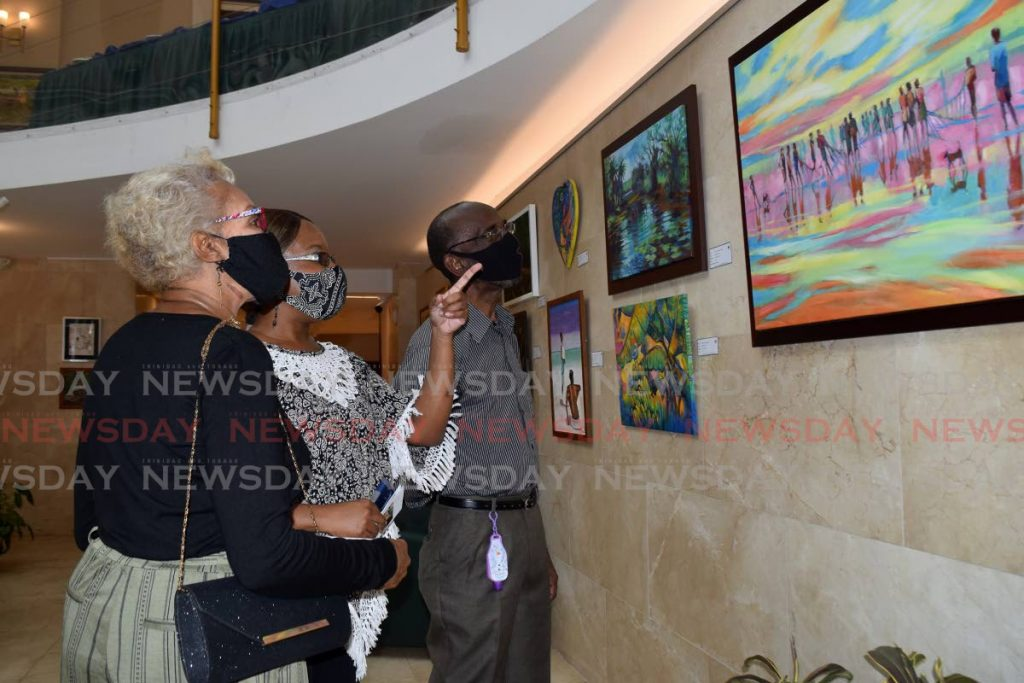 Margot, Latoya and Russell Tidd look at art works on display at the art exhibit 'See the Beauty Around Us... Caring for our Environment' at the Rotunda gallery, Red House, Port of Spain on Wednesday morning. - Photo by Vidya Thurab