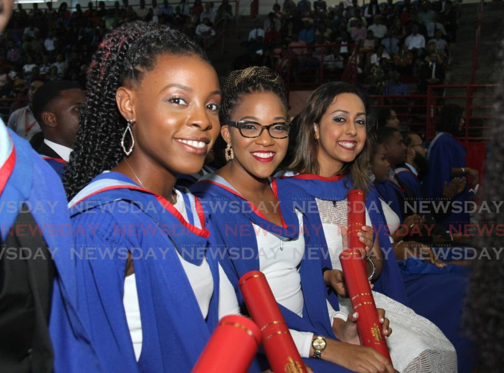 FILE PHOTO: UWI Visual Arts graduates, from left, Akilah Gomez, Anesha Garcia and Rachel Christa Gangadeen display their scrolls at their graduation the St. Augustine Campus, October 26, 2019. A report suggests UWI students should pay 40 per cent rather than 20 per cent of their tuition costs. -